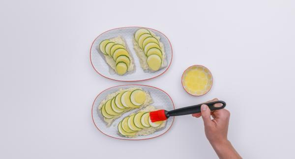 Mescolare il formaggio cremoso con il Parmigiano e il tuorlo e distribuire il composto sui filetti di pesce. Adagiare le fette di zucchina e patate sul pesce, come se fossero delle scaglie, e spennellarele con il burro rimasto.