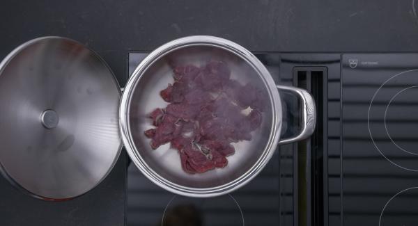 Al suono di Audiotherm, abbassare il calore, rosolare la carne in porzioni, estrarla, condirla con sale e pepe e tenerla in caldo.