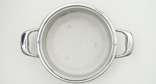 """Usando un coperchio 24 cm come sagoma, ritagliare un disco di carta da forno e inserirlo nell'Inserto """"2 in 1""""."""