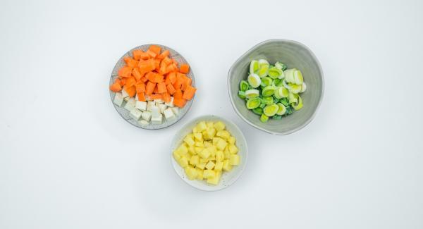 Pelare e tagliare a dadini le patate, le carote e il sedano. Mondare il porro e tagliarlo ad anelli.