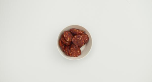 Sbucciare la cipolla e l'aglio, tritarli finemente con Tritamix. Tagliare il chorizo a metà per il lungo, togliere la pelle e tagliarlo a fettine.
