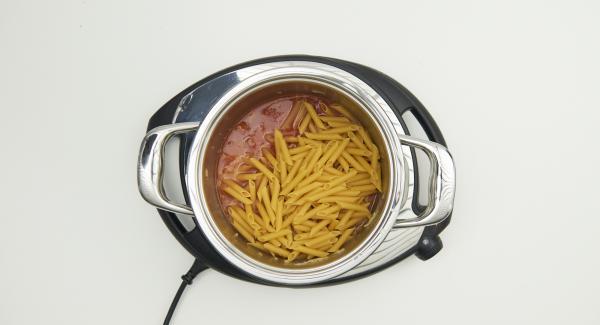 Al suono di Audiotherm, abbassare Navigenio a livello 2, mescolare e rosolare il misto di cipolla e aglio e aggiungere le fette di chorizo. Aggiungere la paprika, la passata di pomodoro, l'acqua, la pasta e la foglia di alloro. Mescolare bene il tutto.