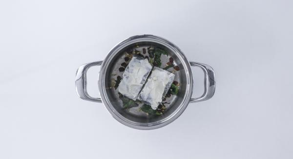 Posizionare il baccalà nell'unità di cottura sopra gli spinaci, con il lato spalmato di salsa aioli rivolto verso l'alto.