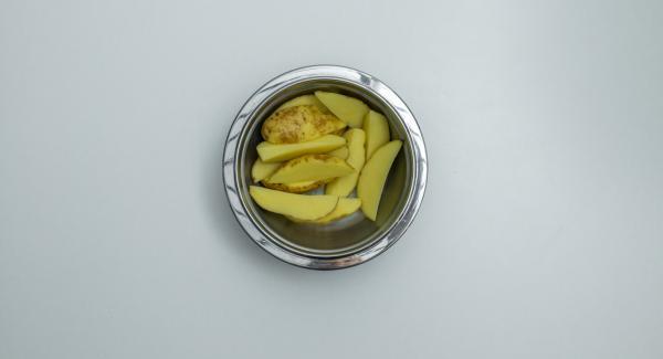 Tagliare a pezzi il pollo e mescolarlo con la pasta di curry. Lavare e spazzolare bene le patate e tagliarle a spicchi.