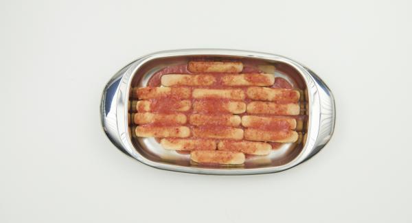 Disporre uno strato di savoiardi nella Lasagnera media, distribuirvi sopra metà della salsa di fragole e attendere che si impregnino bene. Nell'attesa, affettare le fragole rimaste.
