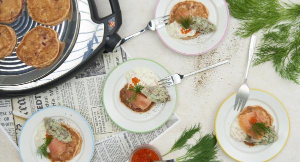 Impiattare le focaccine con la tartare, il caviale di trota e il salmone affumicato e completare con l'aneto.