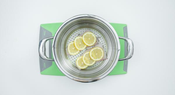 """Tagliare a metà il filetto di pesce, insaporirlo con sale e pepe e adagiarlo nell'inserto """"2 in 1"""". Lavare il limone, tagliarlo a fette e disporle sopra il pesce."""
