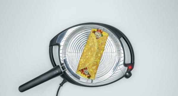 Cospargere con il formaggio grattugiato e il mix di verdure. Arrotolare e servire l'omelette.