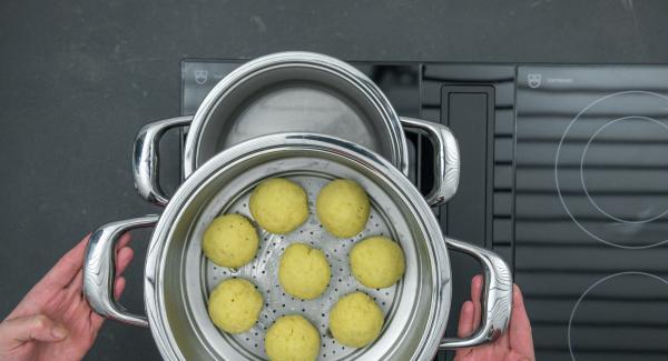 """Formare otto gnocchi di grandezza uniforme, disporli in un inserto """"2 in 1"""" e coprire con un coperchio 24 cm. Versare un'altra tazza d'acqua nell'unità di cottura e inserire l'inserto """"2 in 1""""."""
