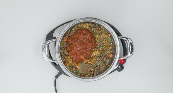 Aggiungere il trito di verdure e cipolla e rosolare il tutto. Unire la passata di pomodoro e cuocere a calore alto per breve tempo. Aggiungere la polpa di pomodoro e il brodo e mescolare bene.