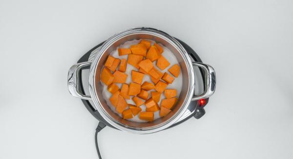 Inserire il disco di carta da forno nell'Unità di cottura, distribuirvi sopra la zucca a pezzi e collocare l'Unità di cottura nel suo coperchio capovolto.
