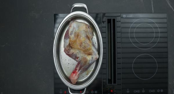 Al suono di Audiotherm, rosolare uniformemente il cosciotto di agnello a fuoco basso. Insaporirlo con sale e pepe e spalmarvi sopra la pasta speziata. Aggiungere le verdure insieme con la foglia di alloro, il brodo e il vino rosso.