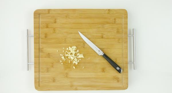 Pestare l'aglio e tagliare il pesce a bocconcini.