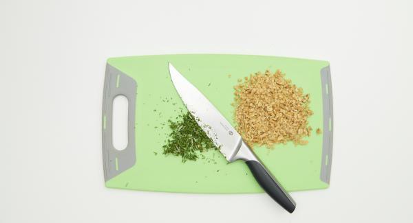 Tritare finemente le noci e sistemarle in una bacinella Combi 16 cm. Tritare finemente le erbe aromatiche.