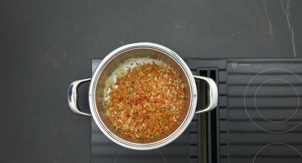 Al suono di Audiotherm, abbassare il calore e rosolare il trito di cipolla e aglio, aggiungere le restanti verdure e la passata di pomodoro e continuare a rosolare.