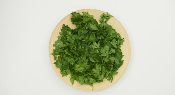 Lavare il prezzemolo, asciugarlo bene e staccare le foglie.