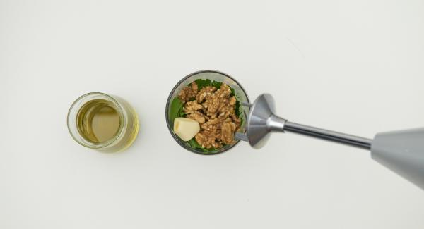 Pelare l'aglio e metterlo in un bicchiere alto e stretto insieme con il prezzemolo e le noci. Tritare finemente con un frullatore a immersione, quindi aggiungere l'olio extravergine di oliva poco alla volta, fino a ottenere un pesto sottile.