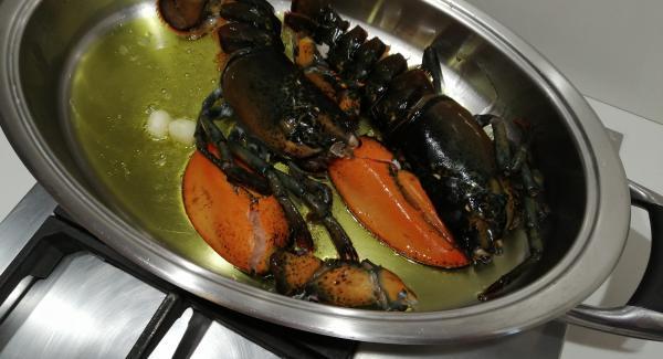 Adagiare l'astice tagliato a metà nell'olio e far rosolare fino al settore carota e tenere sul fuoco abbassando la fiamma per 3 minuti