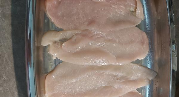 Adagiare un filo di olio extravergine e con un tovagliolo stenderlo per poi adagiarvi le fettine di petto di pollo