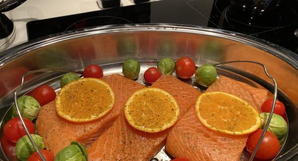 Adagiare le fette di salmone aggiungere i pomodorini e i cavoli di Bruxelles. Mettere sopra al salmone le fette di arancia e distribuire a piacere le spezie AMC